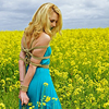 stickpenalties: person wearing a blue dress and some upper-body rope bondage. They are standing in a field of yellow flowers. (bound person in a field of flowers (sfw))