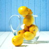 indeliblesasha: Bright blue background with lemons filling and spilling out of a glass pitcher. (Misc - Summer Lemons)