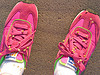serenissima: feet wearing bright pink sneakers, covered with burrs (pink sneakers)