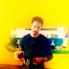 daphnie_1: Tony, yellow background, holding a glass of scotch (Marvel | Tony | Want a drink?)