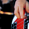 words_unravel: closeup of jon's hands on his bass (fingers & bass)