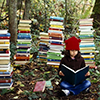 muccamukk: Girl sitting on a forest floor, reading a book and surrounded by towers of more books. (Politics: So Many Books)