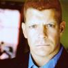 cujothebigreddog: big redhead man with blue eyes, slightly scowly neutral expression, head on (Suspicious)