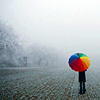 st_aurafina: Rainy day, person with a rainbow umbrella in the distance  (Rainbow umbrella)