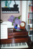 glinda_w: photo of my piano, with a vase of lilacs next to the metronome and my grandmother's chime clock, poster over it (Default)