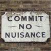 "maewyn: a peeling wooden sign on a brick wall; text: ""commit ~no~ nuisance"" (commit no nuisance)"