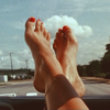 maewyn: bare feet resting comfortably on the dashboard of a car, with white clouds and blue sky in the background (feet on the dashboard)