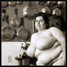 katarik: Naked fat White woman sitting by a kitchen table, pots gleaming on the wall behind her. (Kitchen lives.)