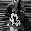 highways: [A black and white image of a woman wearing an oversized Mickey Mouse sweatshirt.] (STOCK ☌ fade to black.)