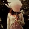 cream_kittens: A girl with long brown hair wearing a white sweater and holding a giant stick of cotton candy. (Ramie)