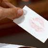 "recessional: a white business card with a lipstick print on it (tv: ""is this your card?"")"