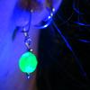 ide_cyan: one of my uranium glass earrings under UV light (Ouraline)
