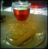 butterflydreaming: A cup of tea in a clear cup, with a plate of tea cookies (Tea & Cookies)