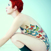 tree: a red haired woman side on showing butterfly tattoos down her torso ([else] embodiment)