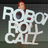 dancesontrains: A white man holding a large sign saying 'ROBOT ROLL CALL' (Robot Roll Call!)