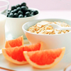 goodbyebird: White bowls with blueberries and oatmeal, plus some slices of orange. A tall glass of milk is visible on the left. (STOCK foodsies!)
