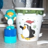 twotone: A toy figure in a penguin costume is dismayed. It stands next to a mug with a penguin illustration and a broken handle. (Default)
