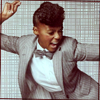 were_duck: musician Janelle Monae singing in a grey jacket (Janelle Monae dynamo in a suit)