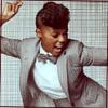 were_duck: musician Janelle Monae singing in a grey jacket (Janelle Monae dynamo in a suit)