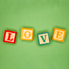 "torch: the word ""love"" in baby blocks on a green background (love is all you need)"