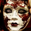 bruised_petals: a woman with cloudy eyes wearing a carnival mask with designs painted in a color similar to blood. (mask)