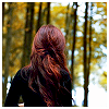 crimson_lily: Backshot image of a woman with dark red hair highlighted with copper in a black sweater, looking at dark woods (Me)