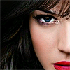 sweet_betrayal: Close up of a brown haired woman, with red lipstick and one blue eye showing. (Default)