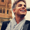 sohotbertfestmods: Light-haired Adam Lambert in a black jacket and thin, light gray scarf, with a microphone in front of him (Blond Adam - Scarf)