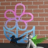 hummingwolf: hummingwolf in front of brick wall with flower drawn on it (Wallflower)