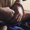 upasika: The hands of a person praying with a mala, Buddhist prayer beads. (mala)