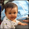 kate_nepveu: infant standing with one hand on couch, smiling at camera (The Pip - standing and smiling (2012-09))
