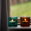 jules_robin: Two votive candles sitting on a windowsill, one in a teal glass the other in a brown glass. (Candles in the window)