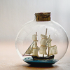 quillori: photo of a ship in a small, round bottle (subject: ship in bottle, theme: travel (ship in bottle), theme: boats (bottled))