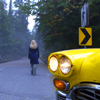 seven: Amanda in the background walking away from a taxi in the foreground in to the woods. (Caprica: End of line.)