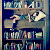 mokie: A child lays in a bed built into a bookshelf, reading (reading)