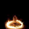 solitarysloth: On a black background, a man standing in a ring of fire (Coming home)