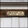 "recessional: a photograph of a sign on a fence saying ""beware attack cow"" (personal; be afraid be very afraid)"