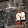 thecolourclear: two girls holding hands in front of a rock face that has water cascading down it (general: handholding)