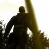 gtfostalker: A man stands in the sunlight, with an unfocused blade of grass in the foreground (Into the Light)