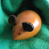 fred_mouse: Wooden mouse shape with leather ears and dots for eyes, wrapped in a piece of green blanket (blanket)