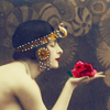 heathertwig: profile of a woman with a 20s egyptian inspired headpiece holding a red rose in her outstretched hand (Default)