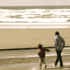 sara: A parent and child walking on the beach (walk on the beach)