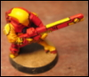 metahacker: A small figurine with a big gun, painted bright yellow and red (tau)