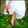 vividoceantides: A woman in a white dress adjusting her red shoes. (red shoes, white dress)