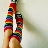 sansets: Knee high rainbow socks on a white person's legs, while the legs are toe-ing a pair of sneakers off. (Default)