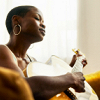 liviconnor: A black woman playing the acoustic guitar with her eyes closed (Guitar rest)