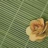 auburn: Yellow rose against green rattan matt (Rattan Rose)