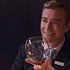 pinesandmaples: Restaurant Manager James smiles with a wine glass in front of his face.  (Hotel Babylon: James giggles)