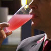 pinesandmaples: Concierge Tony drinks a bright pink cocktail from a champaign flute. (Hotel Babylon: Tony sips)