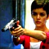 labellementeuse: a slim woman with a dark pixie cut points a gun towards the camera (heroes girls with guns 2.0)